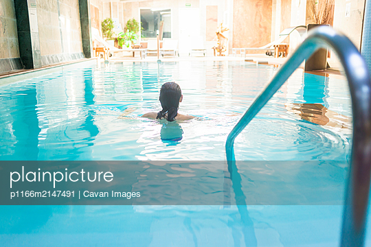 Rear view of a woman relaxing in spa pool - p1166m2147491 by Cavan Images