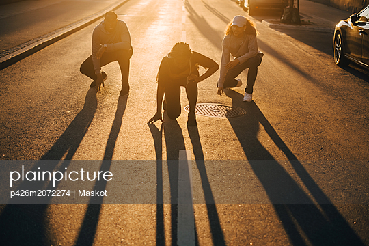 Full length of friends dancing on street in sunlight during sunset - p426m2072274 by Maskot