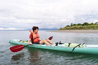Teen relaxing in kayak in Costa Rica - p1166m2189658 by Cavan Images