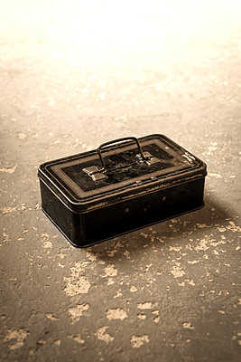 Old money box on a stone floor - p1228m1169454 by Benjamin Harte