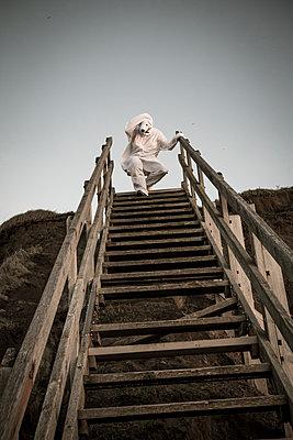 Man wearing ice bear costume on steps, despair - p300m2069517 von realitybites