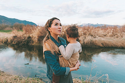 Mother holding her little daughter affectionately in nature - p300m2102778 by Crystal Sing