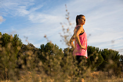 Beautiful woman with hand in hip looking away during sunset - p300m2273465 by Andrés Benitez