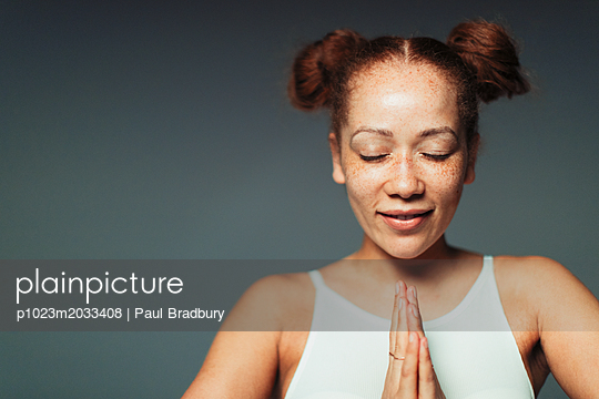 Portrait serene woman with freckles meditating with eyes closed - p1023m2033408 by Paul Bradbury