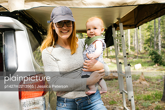 Portrait of smiling woman with baby son (6-11 months) on camping Wasatch-Cache National Forest - p1427m2213565 by Jessica Peterson