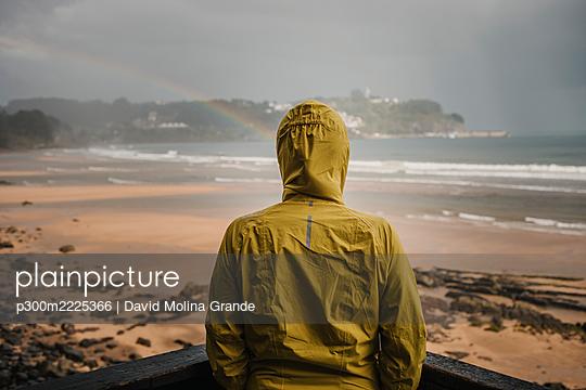 Rear view of woman wearing raincoat by retaining wall during rainy season - p300m2225366 by David Molina Grande