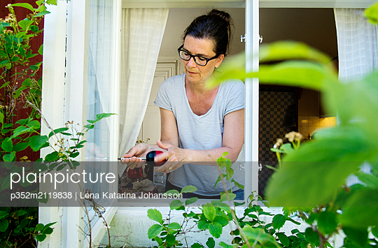 Mature woman drilling window - p352m2119838 by Lena Katarina Johansson