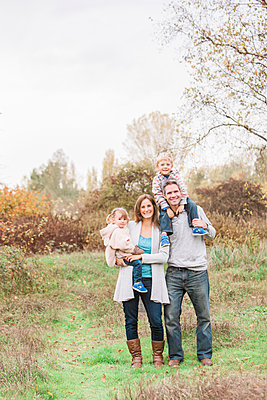 Portrait smiling family in autumn park - p1023m1121374f by Monashee Alonso