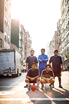 Portrait soccer players standing at city street - p1166m1098370f by Cavan Images