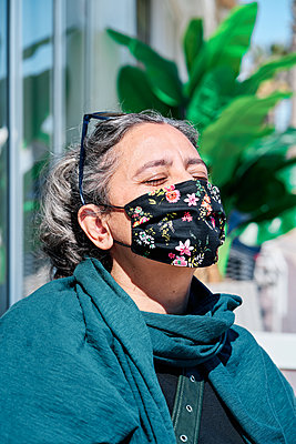 Portrait of a middle-aged woman with white hair, closed eyes and a mask. - p1166m2279276 by Cavan Images