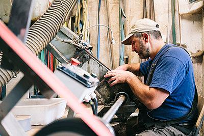 Craftsman making knives in his workshop - p300m2180128 by Daniel González