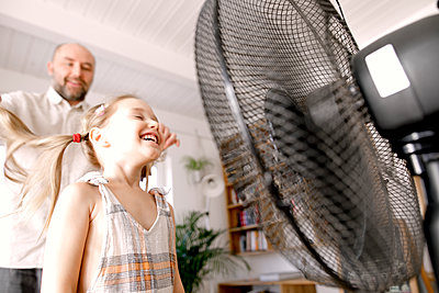 Girl in front of electric fan while father standing at home - p300m2256101 by Katharina Mikhrin
