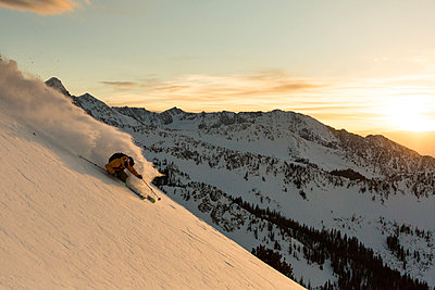 Extreme skier skiing down slope at sunset - p343m1443458 by Wray Sinclair