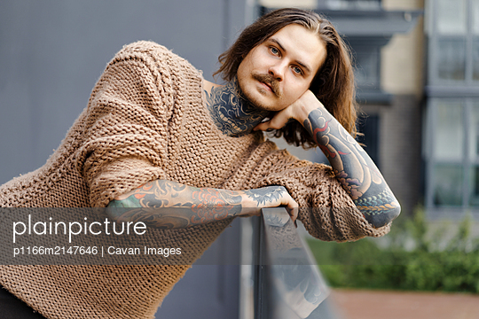 Handsome tattooed sexy man with long hair and mustache outdoors - p1166m2147646 by Cavan Images