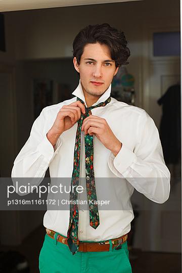 Junger Mann zieht sich an, Hemd und Krawatte - p1316m1161172 von Christian Kasper