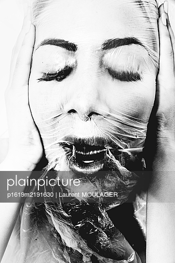 Woman' head wrapped with plastic - p1619m2191630 by Laurent MOULAGER
