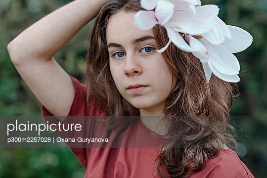 Girl with blue eyes wearing magnolia flower in hair - p300m2257028 by Oxana Guryanova