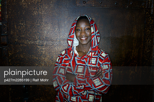 African woman in hooded shirt, portrait - p427m2285199 by Ralf Mohr