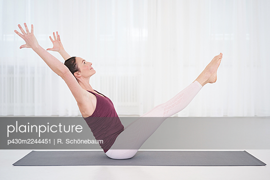 Woman practicing yoga in gym - p430m2244451 by R. Schönebaum