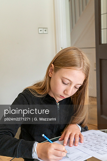 UK, Surrey, Girl (10-11) doing homework at home - p924m2271271 by G. Mazzarini