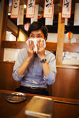 Man sitting at a table in a restaurant, wiping his face with wet towel. - p1100m1531118 by Mint Images