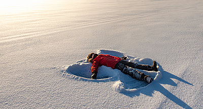 Child making a snow angel in an open snowy field in the morning sun. - p1166m2255306 by Cavan Images