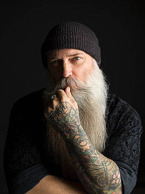 Portrait serious tattooed hipster man with long gray beard against black background - p1192m1403572 by Hero Images
