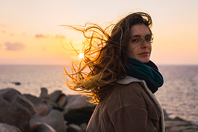 Italy, Sardinia, portrait of woman at the coast at sunset - p300m1580708 by Kike Arnaiz
