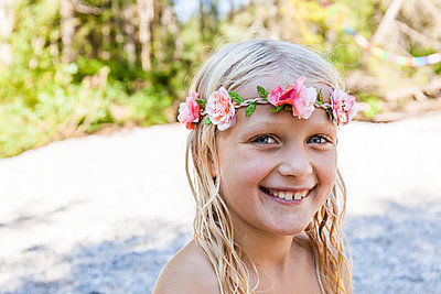 Portrait of happy girl wearing flower crown outdoors in summer - p300m2030366 by Tom Chance
