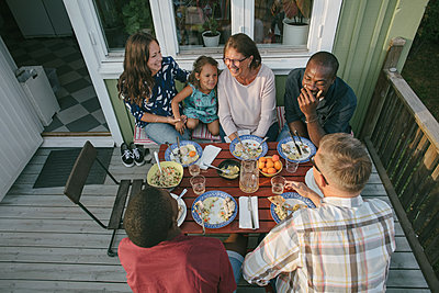 High angle view of multi-generation family having lunch at table on porch - p426m2036537 by Maskot