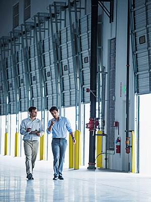Businessmen walking with clipboard near open loading dock doors - p555m1305145 by Erik Isakson