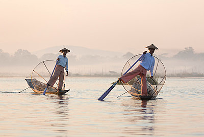 Intha 'leg rowing' fishermen at dawn on Inle Lake who row traditional wooden boats using their leg and fish using nets stretched over conical bamboo frames, Inle Lake - p871m819404 by Lee Frost