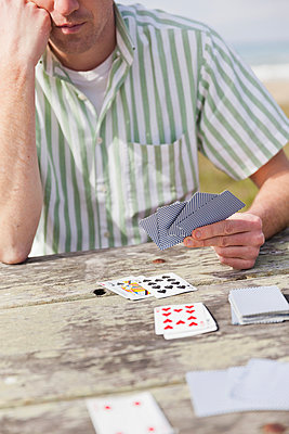 Man playing cards - p956m1044289 by Anna Quinn