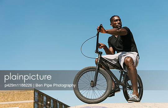 Young man on BMX bicycle looking over his shoulder in skatepark