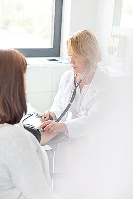 Doctor checking patientÕs blood pressure in examination room - p1023m1086285f by Agnieszka Wozniak