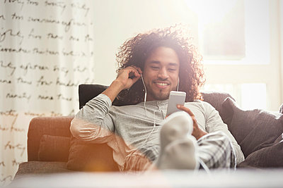 Young man relaxing, listening to music with headphones and mp3 player on sofa - p1023m2161300 by Agnieszka Olek
