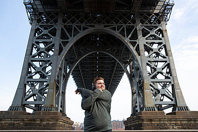 Overweight man stretching arms while standing below Williamsburg Bridge in city - p1166m1576360 by Cavan Images