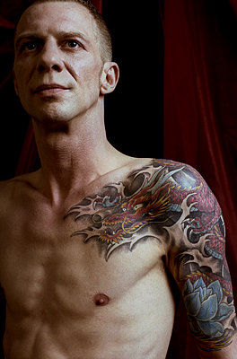 Man with dragon tattoo on shoulder  - p1210m2124991 by Ono Ludwig