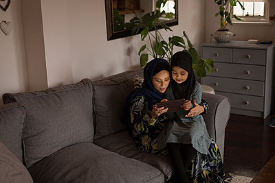 Muslim mother and daughter using digital tablet - p1315m2018379 by Wavebreak