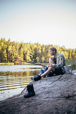 Father and daughter fishing at lake during weekend - p426m2213213 by Maskot