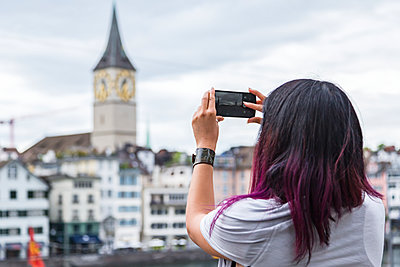 A female tourist takes a landscape photo with her phone while on vacation; Zurich, Switzerland - p442m1449187 by Alanna Dumonceaux
