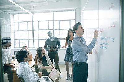 Businessman writing on whiteboard in meeting - p555m1504096 by John Fedele