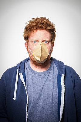 Man wearing coffee filter as protective mask, portrait - p930m2253768 by Ignatio Bravo