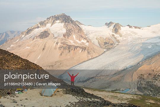 Man enjoys epic campsite with mountain view. - p1166m2153480 by Cavan Images