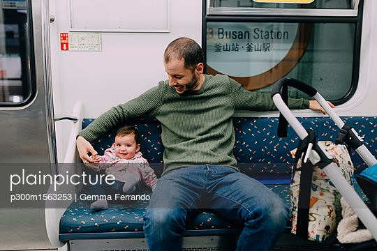 South Korea, Busan, father and baby girl traveling by subway with a stroller - p300m1563253 by Gemma Ferrando