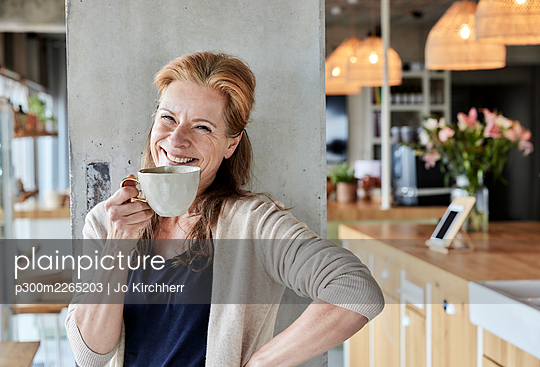 Happy mature woman with hand on hip having coffee against column at home - p300m2265203 by Jo Kirchherr