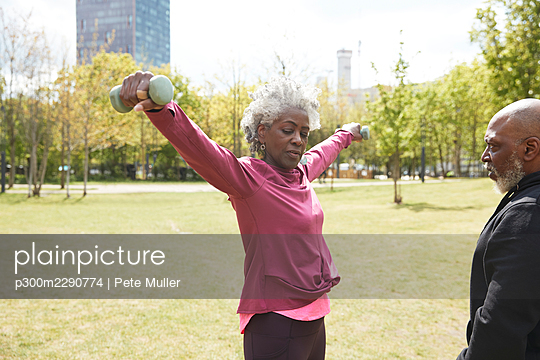 Man looking at senior woman exercising with dumbbells in park - p300m2290774 by Pete Muller