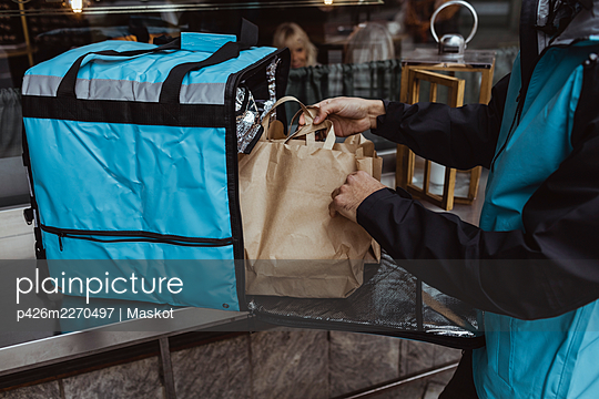 Midsection of delivery man putting package order in backpack outside deli store - p426m2270497 by Maskot