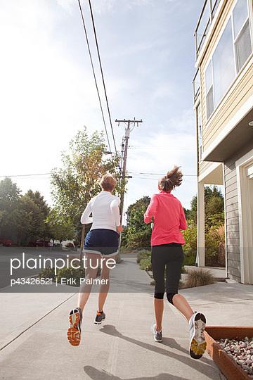 Athletic teen girl and mother running on urban sidewalk