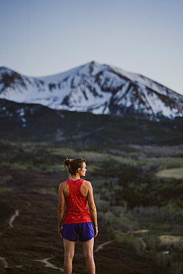 Young woman looks out at the mountains while trail running at dusk - p1166m2247284 by Cavan Images